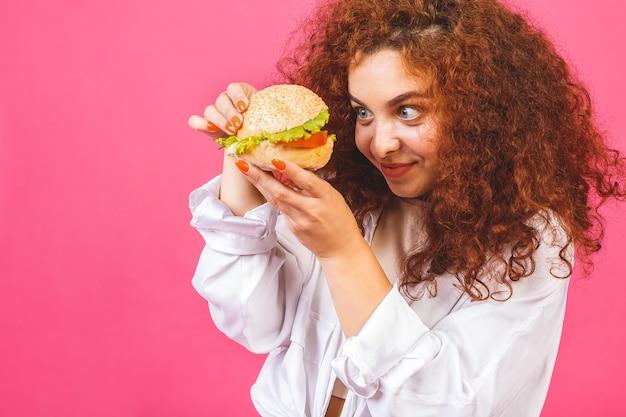 Mulher jovem e atraente e cacheada segurando um hambúrguer grande