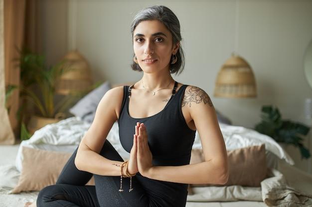 Mulher jovem e atraente e elegante com tatuagem praticando ioga matinal em casa, sentada no chão do quarto, fazendo ardha matsyendrasana