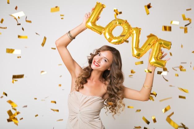 Mulher jovem e atraente e elegante comemorando o ano novo, segurando balões de ar, cartas de amor, confetes dourados voando, sorrindo, feliz, isolada, usando vestido de festa