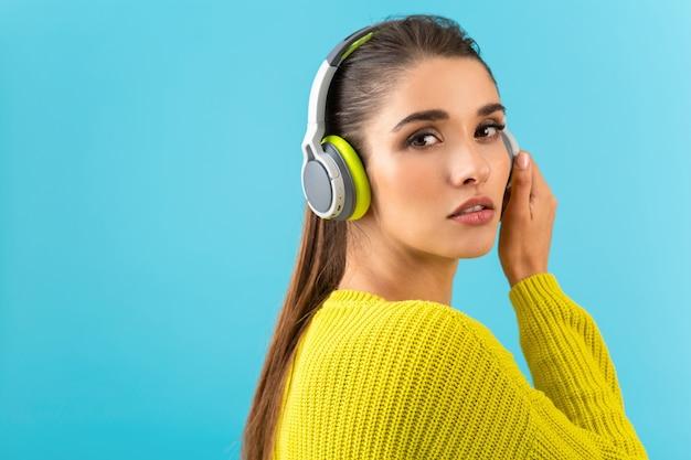 Mulher jovem e atraente e elegante ouvindo música em fones de ouvido sem fio feliz vestindo suéter de malha amarela colorido estilo posar