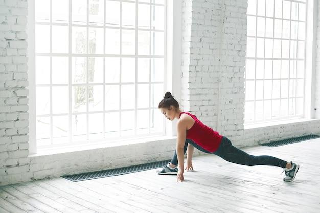 Mulher jovem e atraente e flexível em roupas esportivas, aquecendo as pernas antes da divisão frontal. menina morena alongando os músculos após o treino cardiovascular, em pé fazendo exercícios de baixa estocada ou anjaneyasana perto de uma janela