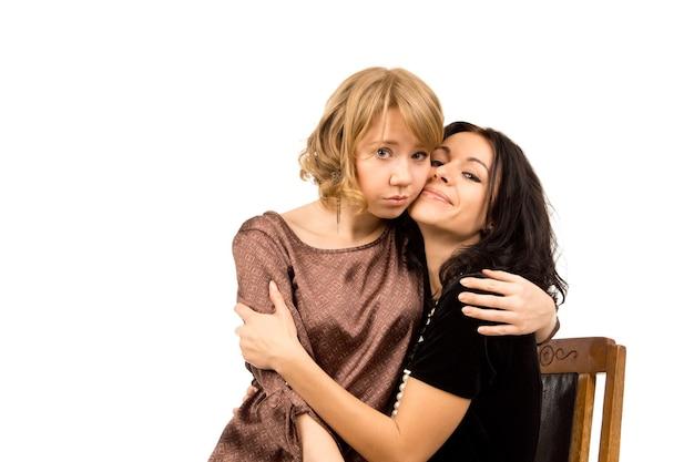 Mulher jovem e atraente e triste sendo consolada por uma amiga que está sorrindo na tentativa de animá-la