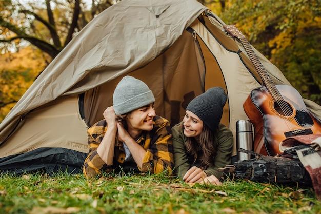 Mulher jovem e atraente e um homem bonito deitado na tenda