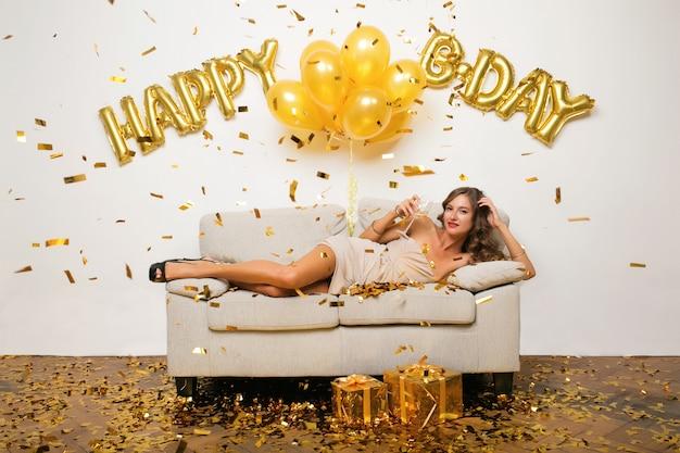 Mulher jovem e atraente elegante comemorando aniversário, sentada no sofá com presentes, confetes dourados e airballons, clima de festa, sorrindo feliz, usando vestido de festa, bebendo champanhe