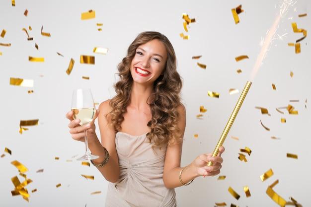 Mulher jovem e atraente elegante comemorando ano novo, bebendo champanhe, confete dourado voando, sorrindo feliz, isolada, usando vestido de festa