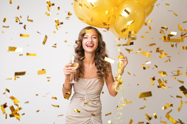 Mulher jovem e atraente elegante comemorando ano novo, bebendo champanhe segurando balões de ar, confete dourado voando, sorrindo feliz, branco, isolado, usando vestido de festa