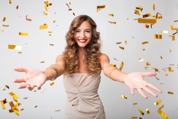 Mulher jovem e atraente elegante comemorando ano novo, confete dourado voando, sorrindo feliz, isolada, usando vestido de festa, maquiagem e penteado