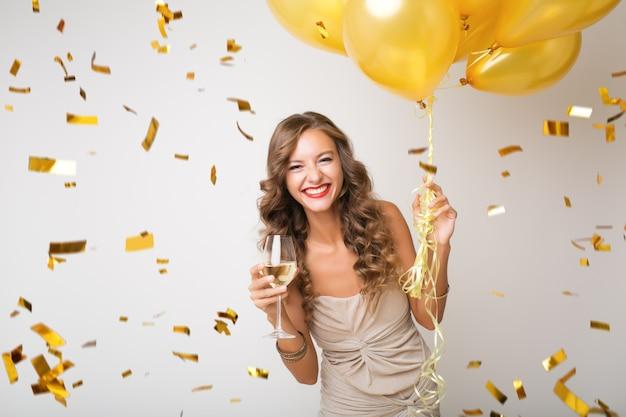 Mulher jovem e atraente elegante comemorando o ano novo, bebendo champanhe segurando balões de ar, confetes dourados voando, sorrindo feliz, isolada, usando vestido de festa