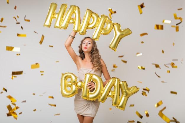 Mulher jovem e atraente elegante comemorando, segurando balões de ar, cartas de feliz aniversário, confetes dourados voando, sorrindo feliz, isolada, usando vestido de festa