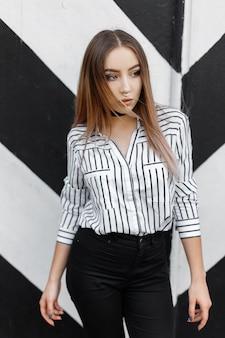 Mulher jovem e atraente elegante em jeans pretos elegantes com uma blusa elegante em uma faixa com um piercing no nariz está parada ao ar livre perto de um edifício vintage na fila