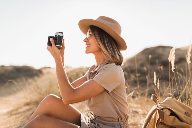 Mulher jovem e atraente elegante em um vestido cáqui no deserto, viajando pela áfrica em um safári, usando chapéu e mochila, tirando foto na câmera vintage, explorando a natureza, tempo ensolarado