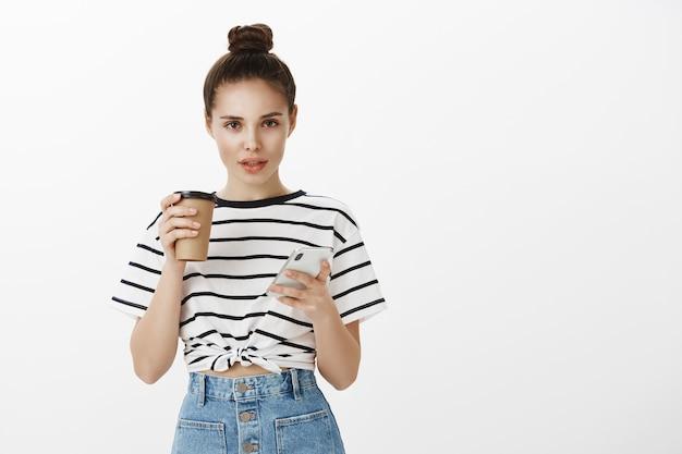 Mulher jovem e atraente elegante usando smartphone e tomando café no café