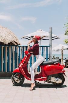 Mulher jovem e atraente elegante vestida de calça branca e camisa com óculos de sol, posando enquanto está sentado na moto vermelha à beira-mar