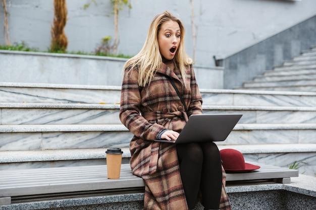 Mulher jovem e atraente em choque, vestindo um casaco, sentada ao ar livre, usando um laptop