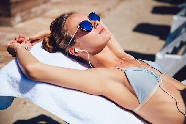 Mulher jovem e atraente em fato de banho e óculos de sol deitado numa espreguiçadeira, leva um bronzeado
