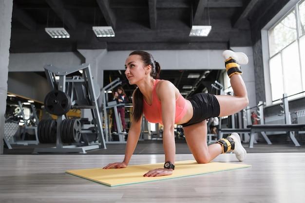 Mulher jovem e atraente em forma dando chutes de burro com pesos nos tornozelos, malhando na academia