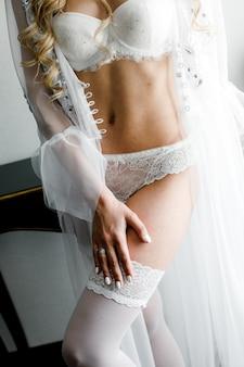Mulher jovem e atraente em lingerie branca linda noiva em lingerie na manhã do dia do casamento