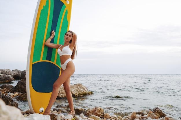 Mulher jovem e atraente em maiô branco posando com prancha de stand up paddle