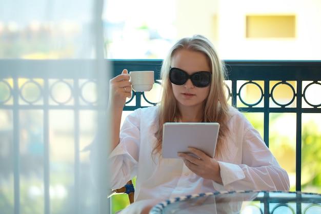 Mulher jovem e atraente em óculos de sol, lendo um tablet pc em uma varanda