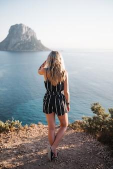 Mulher jovem e atraente em pé em um penhasco à beira-mar durante o dia