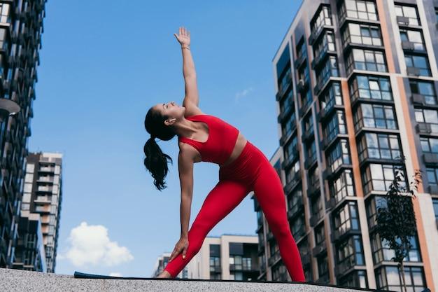 Mulher jovem e atraente em pose de triângulo em um tapete escuro de ioga