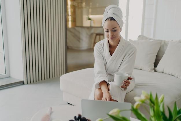 Mulher jovem e atraente em roupão de banho branco e cabelo enrolado em uma toalha relaxando no sofá na sala de estar depois de tomar banho em casa, mulher feliz bebendo chá ou café, usando laptop e sorrindo