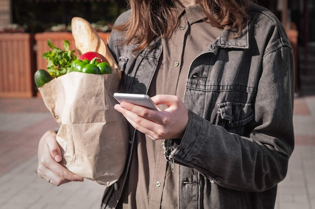 Mulher jovem e atraente em roupas de estilo casual, segurando o saco de papel reciclável de compras compradas no local de vegetais e mercearia ou mercado.