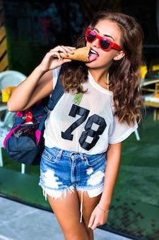 Mulher jovem e atraente em roupas elegantes, posando e olhando. a mulher tomando sorvete ao ar livre, bolsa esportiva no ombro, roupas brilhantes e óculos escuros.