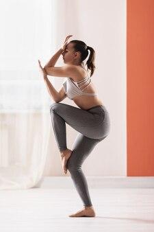 Mulher jovem e atraente em roupas esportivas praticando uma nova técnica em tormento de asana de 9 luas de ioga