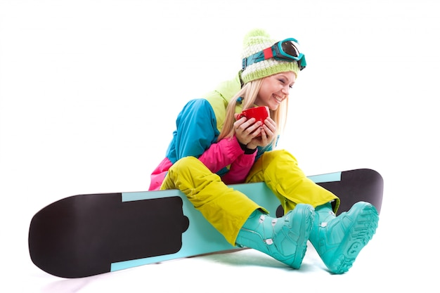 Mulher jovem e atraente em terno de esqui e óculos de esqui sentar no snowboard, segure o copo vermelho