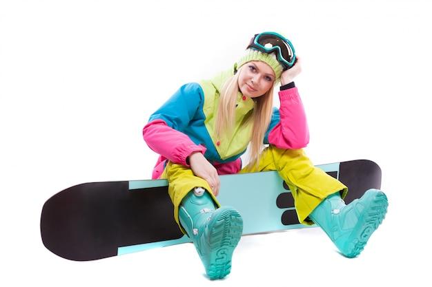 Mulher jovem e atraente em terno de esqui e óculos de esqui sentar no snowboard