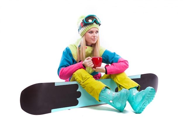 Mulher jovem e atraente em terno de esqui e óculos de esqui sente-se no snowboard, segure o copo vermelho