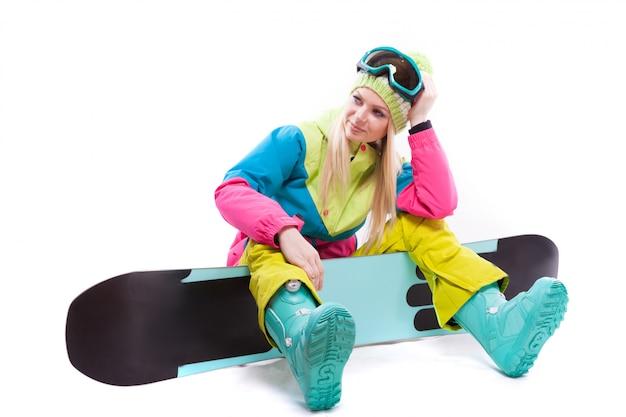 Mulher jovem e atraente em terno de esqui e óculos de esqui sente-se no snowboard