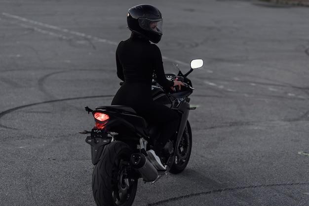 Mulher jovem e atraente em terno preto apertado e capacete protetor facial cavalga na motocicleta de esportes no estacionamento urbano ao ar livre à noite.
