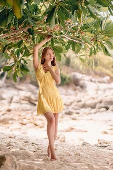 Mulher jovem e atraente em um vestido amarelo posando perto de palmeiras