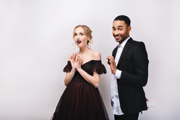 Mulher jovem e atraente em um vestido de noite de luxo com um homem bonito de smoking com presente nas costas. lindo casal brincalhão,