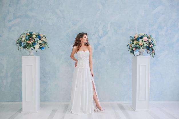 Mulher jovem e atraente em um vestido de noiva. noiva com o bouquet
