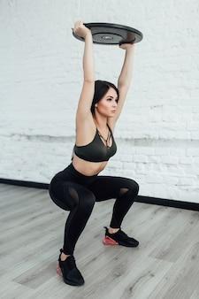 Mulher jovem e atraente em uma academia fazendo agachamentos