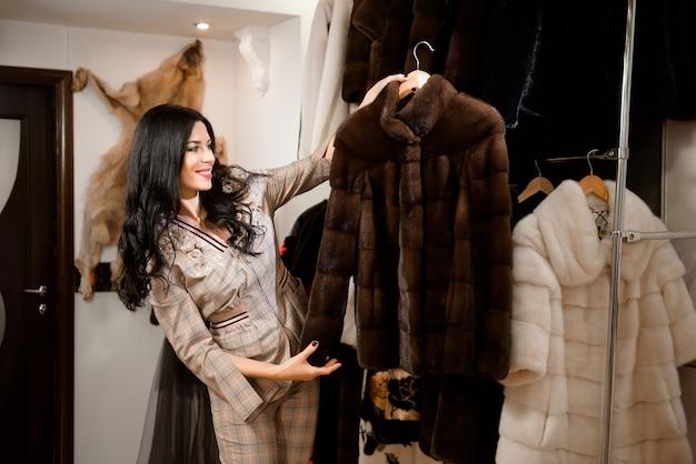 Mulher jovem e atraente em uma loja de casacos de pele com um casaco de pele no cabide