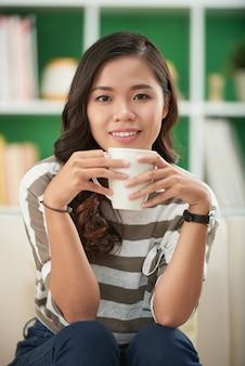 Mulher jovem e atraente encantadora com roupas casuais, sentada no sofá em casa bebendo uma xícara de chá de ervas