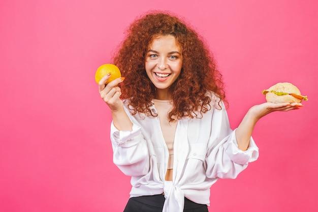 Mulher jovem e atraente escolhe entre alimentos saudáveis e não saudáveis