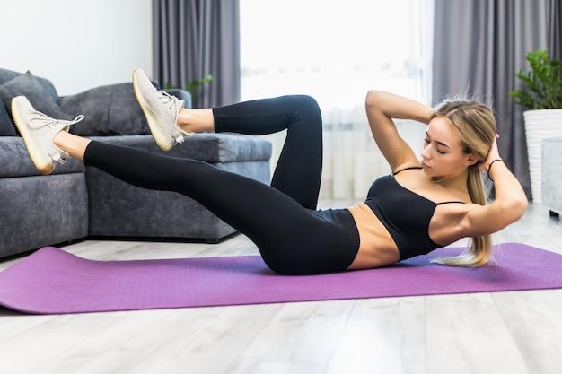 Mulher jovem e atraente está exercitando em sua sala de estar fazendo abdominais enquanto está sentado em uma esteira de exercício.