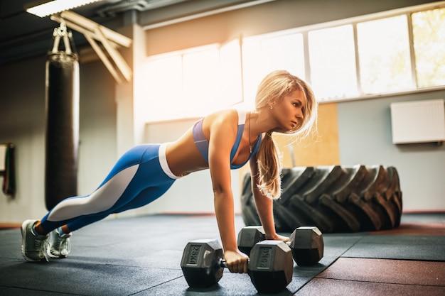 Mulher jovem e atraente está fazendo exercício de prancha enquanto trabalha fora no ginásio