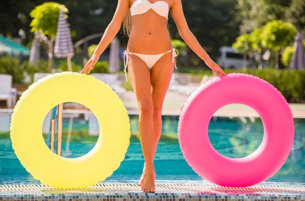 Mulher jovem e atraente está posando com anéis de borracha coloridos