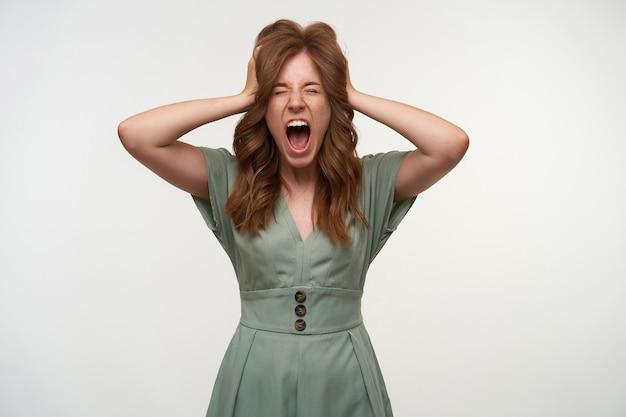 Mulher jovem e atraente estressada com cabelo ruivo posando, segurando a cabeça com as mãos e gritando com os olhos fechados, tendo um dia ruim