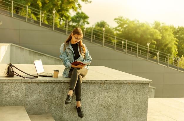 Mulher jovem e atraente estudante está lendo um livro enquanto está sentado na escada na cidade. o conceito de ensino à distância. estudante moderno