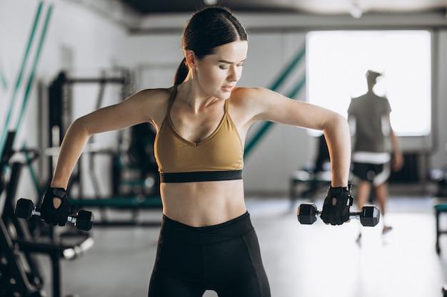 Mulher jovem e atraente exercitando na academia