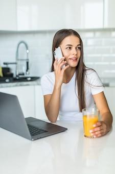 Mulher jovem e atraente falando no celular em pé em uma cozinha com copo de suco