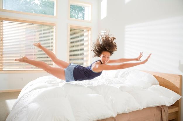 Mulher jovem e atraente fazendo barriga flop na cama