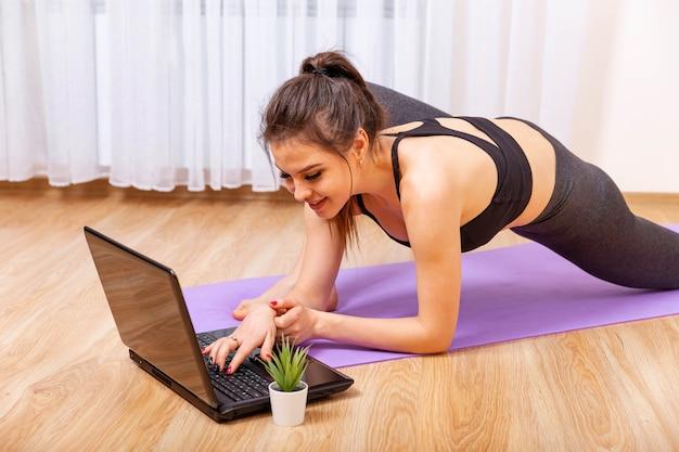 Mulher jovem e atraente fazendo ioga e alongamento online em casa